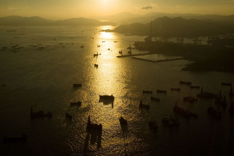 Ships sail through Victoria Harbor at sunset near the the Kwai Tsing Container Terminals, right, in Hong Kong, China. Photographer: SeongJoon Cho/Bloomberg